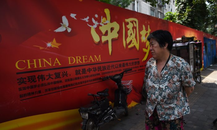 "A woman looks at a banner about the ""China Dream"", Chinese President Xi Jinping's vision for China's future, in Beijing on July 7, 2015. (Greg Baker/AFP/Getty Images)"