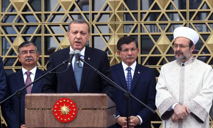"Turkish President Recep Tayyip Erdogan (2L) inaugurates a mosque on the grounds of his gigantic palace complex and opens it to the public in an apparent effort to stave off more criticism over his spending, in Ankara, Turkey, on July 3, 2015. Erdogan, who has been accused of squandering state resources by building the grandiose 1,150-room presidential palace, dedicated the mosque to the people at the opening ceremony, naming it the ""Bestepe People's Mosque."" Prime Minister Ahmet Davutoglu (2R), head of Religious Affairs Mehmet Gormez (R), and new Parliament Speaker Ismet Yilmaz listen. (AP)"