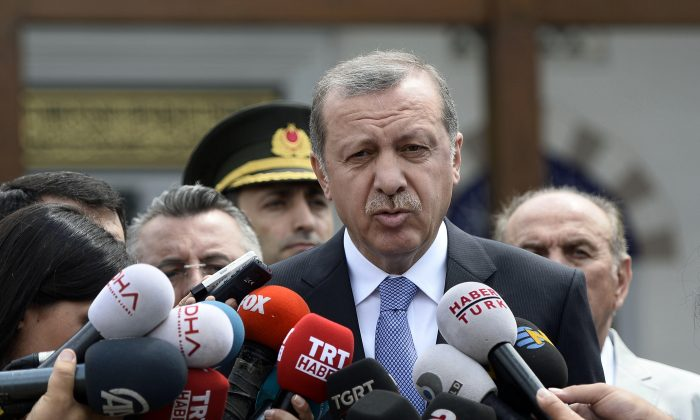 """Turkish President Recep Tayyip Erdogan speaks to the media in front of a mosque in Istanbul, Turkey, on July 24, 2015. In a major tactical shift, Turkish warplanes struck Islamic State targets across the border in Syria on July 24, Turkish officials announced—a move that came a day after ISIS militants fired at a Turkish military outpost, killing a soldier. In a related, long-awaited development, Erdogan confirmed that Turkey had agreed to let the United States use a key base in southern Turkey for military operations against the militants """"within a certain framework."""" (Depo Photos/AP)"""