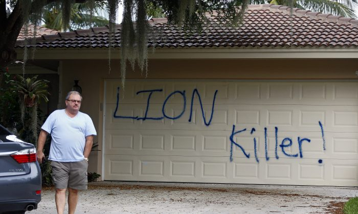 "Private Investigator for the Palmer family, Walter Zalisko, of Global Investigative group in Fort Myers walks out of the home Tuesday, Aug. 4, 2015, at the Marco Island home of dentist Walter J. Palmer. Zalisko said no vandalism was found inside. The home was discovered vandalized with the worlds ""LION Killer!"" and littered with pigs feet drenched in hot sauce. Palmer, a Minnesota resident, is wanted in the killing of Zimbabwe's famous lion, Cecil, a lion who drew thousands of tourists and dollars annually. (Corey Perrine/Naples Daily News via AP)"