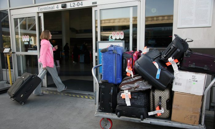 FILE - In this March 27, 2014 file photo, a baggage cart sits outside a terminal at Los Angeles International Airport in Los Angeles. (AP Photo/Nick Ut, File)