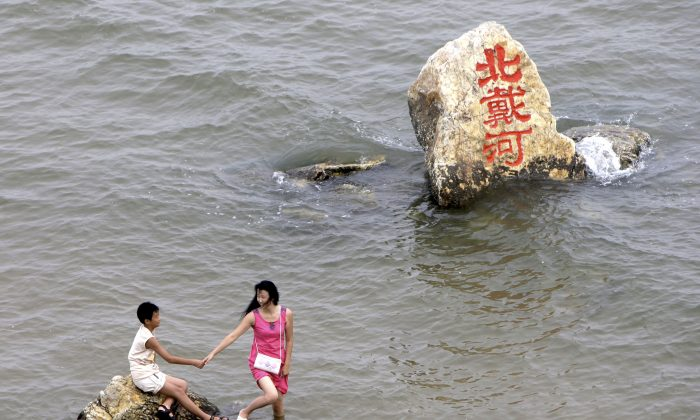 """The Chinese characters in red on the rock read: """"Beidaihe."""" Photo from Aug. 8, 2008. (AP Photo/Silvia Izquierdo)"""