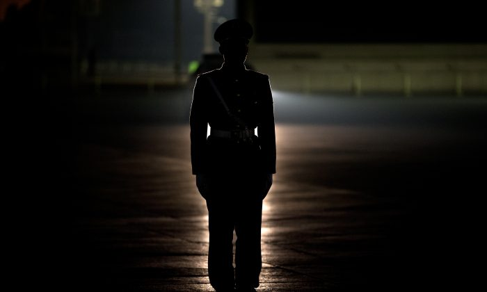 A Chinese paramilitary  stands guard on Tiananmen Square before a flag raising ceremony in Beijing on March 17, 2013. (AP Photo/Andy Wong)