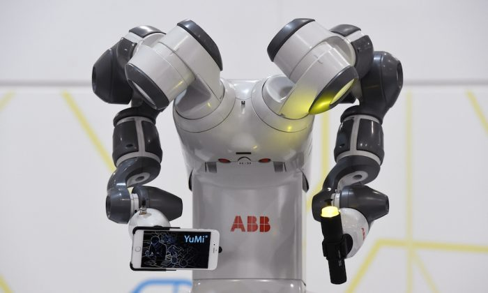 A collaborative dual-arm robot YuMi holding a smartphone and a torch is on display at the Hannover Messe industrial trade fair in Hanover, central Germany on April 13, 2015. Few made in China products were in the limelight at the fair. (TOBIAS SCHWARZ/AFP/Getty Images))