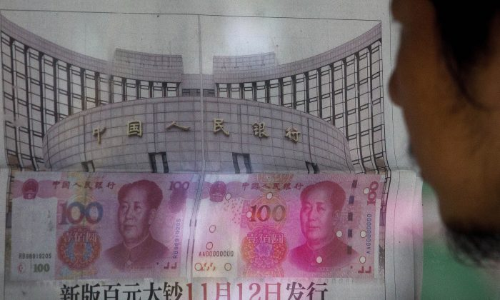 A man reads a newspaper report that China's central bank announced it will devalue China's tightly controlled currency on Aug. 11, 2015 following a slump in trade, triggering the yuan's biggest one-day decline in a decade. (AP Photo/Andy Wong)