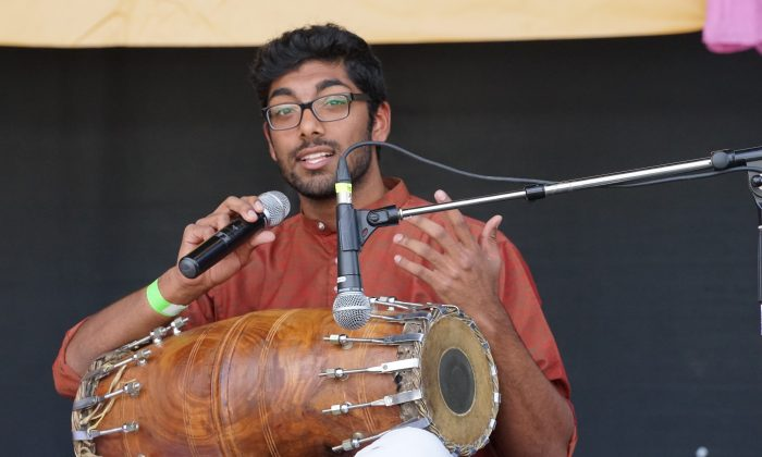 A drummer explains how to play the naal, a wooden drum that requires two-handed playing. (Pam McLennan/Epoch Times)