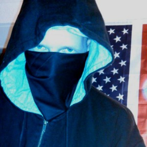 DigitaShadow, an operations director of the hacker group GhostSec, stands in front of an American flag. The organization is fighting ISIS online. (GhostSec)