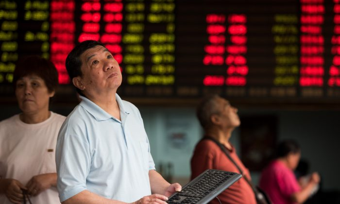 Investors monitor screens showing stock market movements at a brokerage house in Shanghai on Aug. 13, 2015. (Johannes Eisele/AFP/Getty Images)