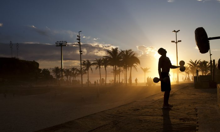 A man works out at sunset at the Arpoador beach in Rio de Janeiro, Brazil, Friday, Dec. 16, 2011. (AP Photo/Felipe Dana)