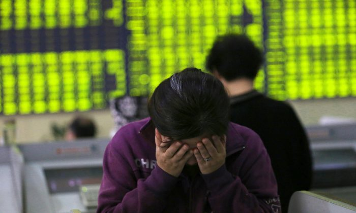 A woman rubs her face as she stands at a computer terminal in a stock brokerage house in Nantong in eastern China's Jiangsu Province, on July 8, 2015. (Chinatopix via AP)