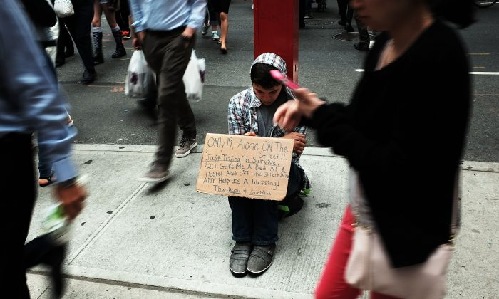 A homeless teen panhandles on a street near Eighth Avenue in Manhattan on May 18, 2015 in New York City. ( Spencer Platt/Getty Images)