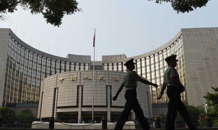 Paramilitary policemen patrol in front of the People's Bank of China, the central bank of China, in Beijing on July 8. (Greg Baker/AFP/Getty Images)