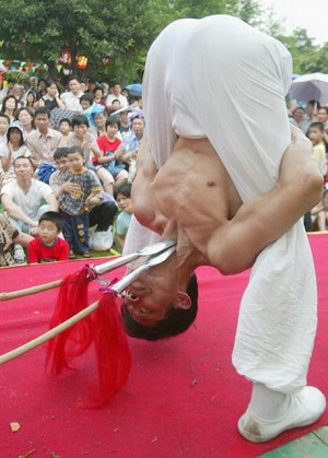 Street performance of stabbing at the throat with spears. (Getty Images)