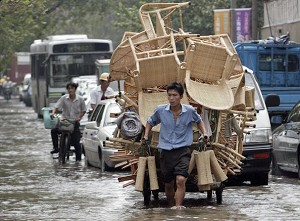 After a typhoon, a peddler pulls goods across the flooded area (Getty Images)