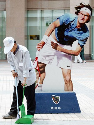 A street cleaner sweeps in front of the oversized image of tennis player Roger Federer (Getty Images)