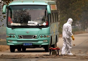 Health workers temporarily disinfect parts of Wantang Village in Xiangtan County, central China's Hunan Province, where a 12-year-old girl died of flu-like symptoms, October 27, 2005. (The Epoch Times)