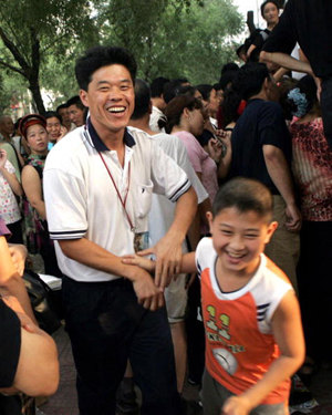 A man celebrates with his son after finding out he qualified for an elite junior school, as parents gather to check if their children are qualified. (AFP/Getty Images)