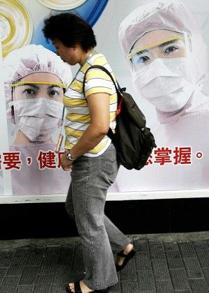 A pedestrian walks past a billboard showing medical workers in protective suits, displayed in front of a local bank in Hong Kong. The sister of the boy who is infected already passed away, but according to Chinese reports, she did not test positive to bird flu. (Ted Aljibe/AFP/Getty Images)