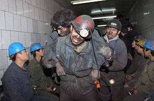 Rescuers assist miner Feng Yin after he was trapped following a blast accident at Dongfeng Coal Mine on November 28, 2005 in suburb of Qitaihe City of Heilongjiang Province, northeast China. (China Photos/Getty Images)