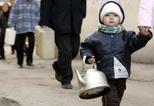 A young boy carries a kettle as residents collect water in the northern Chinese city of Harbin, 25 November 2005,where a spillage of carcinogenic benzene severely polluted one of China's biggest rivers after a chemical plant explosion in the neighbouring province of Jilin causing water supplies in the city to be cut for millions of people.   AFP PHOTO/Peter PARKS