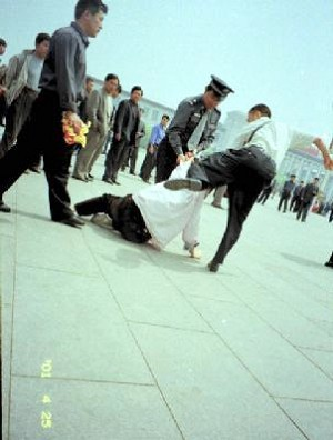 "Plain-cloth police brutally arrest Falun Gong practitioners on Tiananmen Square. ""The 6-10 Office's singular capacity for terror depends, first of all, on the way it penetrates every aspect of Chinese society, from the top to the bottom.""  (Compassion Magazine)"