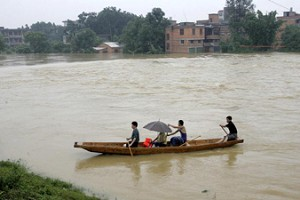 Residents of Fujian residents flee their home, steering their small boat through the flood, June 22, 2005. (Getty Images)