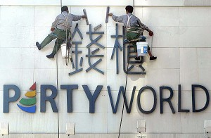 Highrise building exterior cleaners wipe clean a sign for a karaoke entertainment establishment in Beijing. (Frederic J. Brown/AFP/Getty Images)