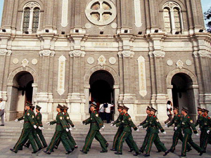 Chinese police march past a State-sanctioned Catholic church in Beijing, (AFP/Getty Images)