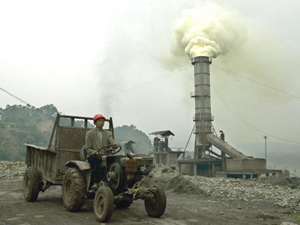 A worker drives a tractor near a smokestack at a cement factory in China&#039s southwestern Sichuan province. (Liu Jin/AFP/Getty Images)