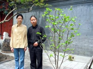 During his final years, Zhao liked pure white magnolia flowers and tended the magnolia tree in the yard. On the first Qingming festival after his death, 26 magnolia flowers suddenly came into full bloom. The picture shows Zhao Xin and Wang Yannan in front of the magnolia tree. (The Epoch Times)