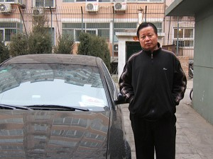 Gao stands next to onew of the plainclothes police vehicles constantly parked in front of his house.  (The Epoch Times)