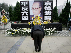 A mourner bows over a large portrait of former Chinese Communist Party chief Zhao Ziyang in Hong KJong's Victoria Park 19 January 2005. (Mike Clarke/AFP/Getty Images)