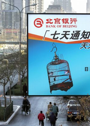 Cyclists ride beneath an advertising billboard for the Bank of Beijing 05 December 2005, in Beijing. (Frederic J. Brown/AFP/Getty Images)