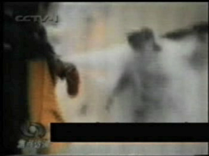 The following 3 sequences, taken from CCTV's own footage shows that Ms. Liu may not have died from the flames, but instead by a blow to the head, delivered by a man in a military overcoat. (NTDTV's False Fire video, showing footage from China Central Television)