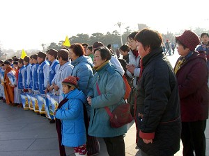 At 10:23 a.m., Buddhist nuns from Mount Wutai took group photos around the monument on the Tiananmen Square. They chanted the name of Buddha Amitaba in chorus. With their hands closed palm-to-palm in a gesture of reverence, many tourists were drawn to the nuns, trying to make karmic relationships. (The Epoch Times)
