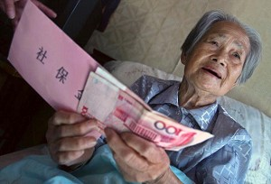 Hu Axiang, 88, receives her first pension at her home on September 28, 2006 in Shanghai, China. 26,788 residents over 70 years of age received their first pension checks after Chen Liangyu, secretary of the Shanghai Municipal Committee of Communist Party of China (CPC), was dismissed for graft involving the city's pension fund and a wide range of other corrupt practices. (China Photos/Getty Images)