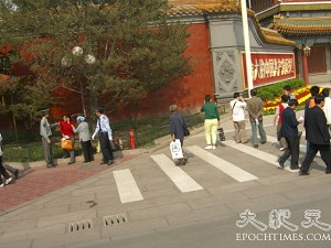 A policeman interrogating pedestrians in front of the Xinhua Gate. (The Epoch Times)