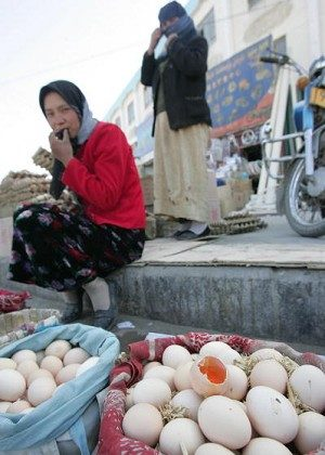 An egg is cracked open for display to show the quality of its yolk as streetside vendors await customers in China's far west Xinjiang Uighur Autonomous Region. The Beijing News recently reported that some duck farmers in Hebei Province, China, feed their ducks with Sudan IV, a poisonous industrial dye, so that their ducks can produce eggs with red yolks. (Frederic J. Brown/AFP/Getty Images)