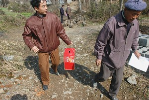 Mobile polling station officials of Fengxing Village carry the ballot box and registration in Fanchang County of Anhui Province, eastern China.  China started the village committee system in 1978, which is supposed to let villagers run their own affairs, but in practice, it is still controlled by the CCP.  (China Photos/Getty Images)
