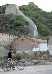 A woman passing by a ruined segment of the Great Wall at Zhang Jia Kou. (Frederic J. Brown/AFP/Getty Images)