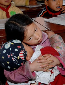 Ning Yuexiang pays attention in class while coaxing her brother to sleep. (The Epoch Times Archive)