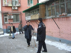 On the afternoon of February 9, while under house arrest, Mr. Qi Zhiyong was making a telephone call at his front door. (The Epoch Times)