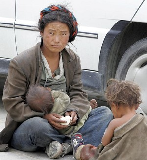 A poor woman breast-feeds her baby outside the Tashilhunpo Monastery in Shigatse, 06 August 2005 in southern Tibet. (Frederic J. Brown/AFP/Getty Images)