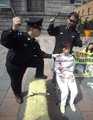 Members of the local Chinese community enact the abuse by Chinese police of a practitioner of Falun Gong,12 September, 2005 in Mexico City. (Juan Barreto/AFP/Getty Images)