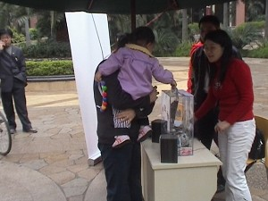People solicit contributions for Li Gang in Meilin Coast Garden on March 5. (The Epoch Times)