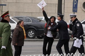 An appellant, waving an application for land compensation, is arrested by plainclothes and armed policemen in Tiananmen Square. (AFP/ Getty Image)