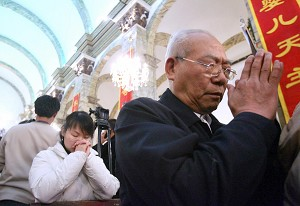 Religion is gradually re-entering Chinese people's lives as people pray in a church in Beijing on 24 December, 2005. (Getty Images)
