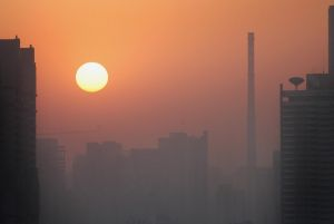 A layer of pollution hovers over Beijing, 05 April 2006, as the sun rises beside a smokestack chimney from a power station. As Beijing gears up to host the 2008 summer games, officials are planning a host of stringent measures to clear the city's badly polluted air - if only for the few weeks the world's elite athletes are in town. (Frederic J. Brown/AFP/Getty)