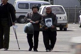 Wang Jianguo's 81-year-old grandmother holds his photo. Wang was tortured to death last month, and she has no avenue to appeal.(Clearwisdom.net photo)