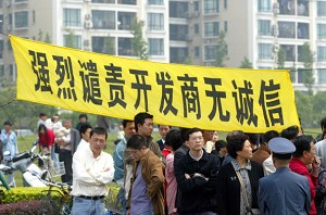 """Owners hang a banner that reads: """"Strongly Condemn the Dishonest Real Estate Developer"""" to protest at the Shanghai Cannes Residential Area May 14, 2006 in Shanghai, China. (China Photos/Getty Images)"""
